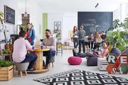 Las personas que trabajan en la agencia moderno que se relaja durante el almuerzo