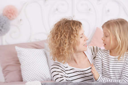 Young mom and her little daughter talking in a bedroom