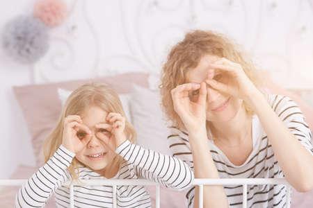 Kleines blondes Mädchen und junge lächelnde lächelnde Frau beim Sitzen auf einem Bett Standard-Bild - 75685519