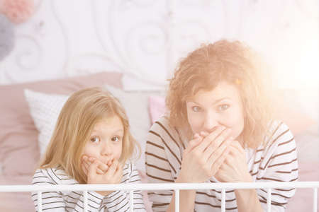 Smiling mom and daughter covering their mouths and sitting in bright bedroom