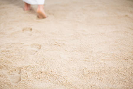 Jesus Christ walking and leaving footrpints in sand 스톡 콘텐츠