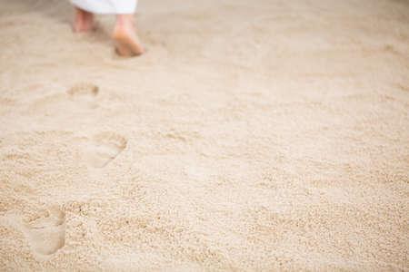 Jezus Christus loopt en verlaat voetprikken in het zand Stockfoto