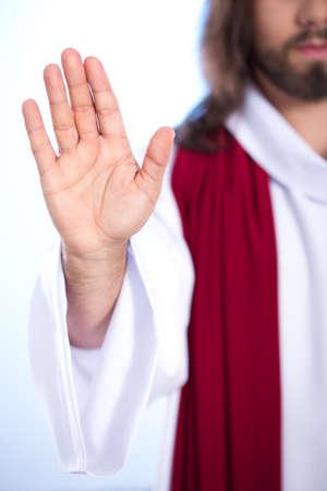 Raised hand of Jesus isolated on bright background Stock Photo