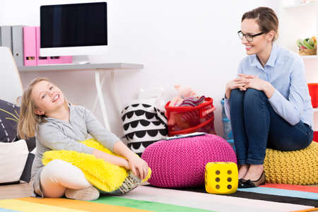 Little blond girl and professional psychologist laughing in an office Stock Photo