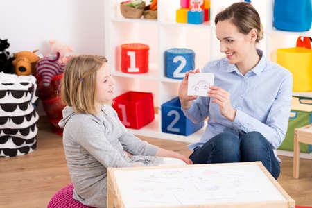 Little blond girl visiting professional speech therapist
