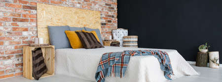 kingsize: King-size bed in spacious bedroom with brick wall Stock Photo