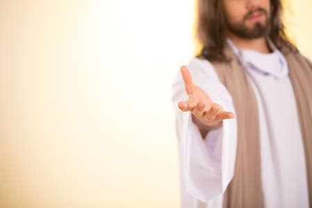 Messias die zijn hand bereikt die op verlichte achtergrond wordt geïsoleerd Stockfoto