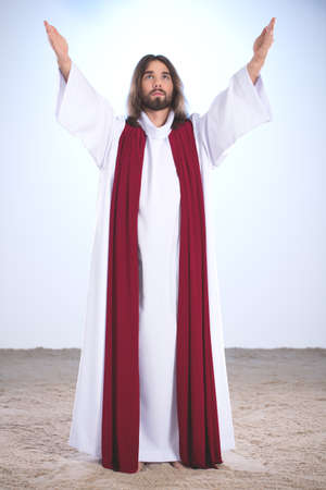 Jesus Christ raising hands to sky, illuminated background