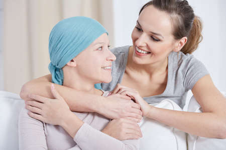 Young woman with blue headscarf looking and smiling at her sister Imagens