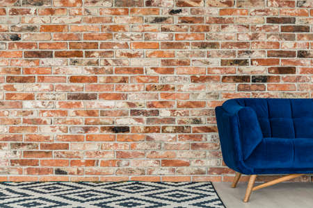 red sofa: Black and white carpet in room with brick wall and blue sofa Stock Photo