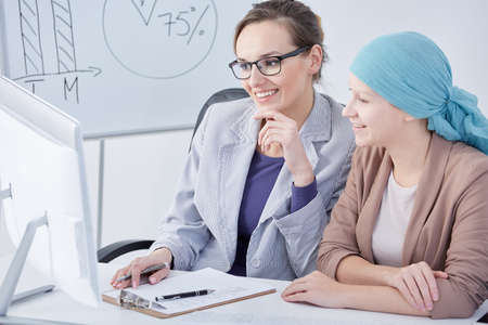 Young professional oncologist and her patient looking at a screen Stock Photo
