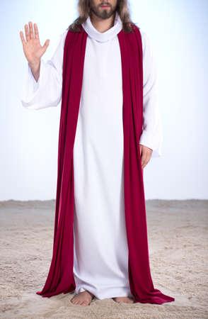 Jesus standing on sand, raising palm of his hand
