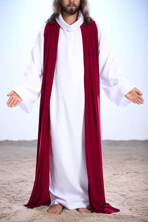 vangelo aperto: Gesù risorto, in piedi sulla sabbia con le braccia aperte