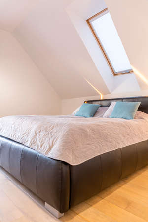 King-size bed in the light bedroom in the loft
