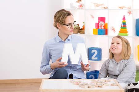 Professional speech therapist helping little blond girl