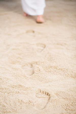 Jésus se promène en laissant ses traces dans le sable Banque d'images - 75795461