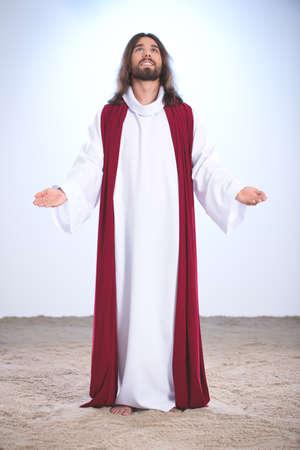 vangelo aperto: Gesù Cristo pregando Dio, tenendo le braccia aperte Archivio Fotografico
