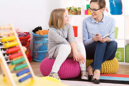 Smiling girl and professional psychologist sitting on poufs in room with toys Stock Photo