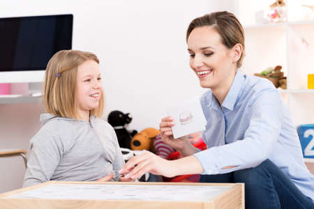 Happy little girl having a lesson with private tutor Stock Photo