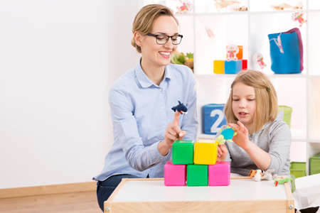 Little girl visiting psychologist and playing with toys Stock Photo