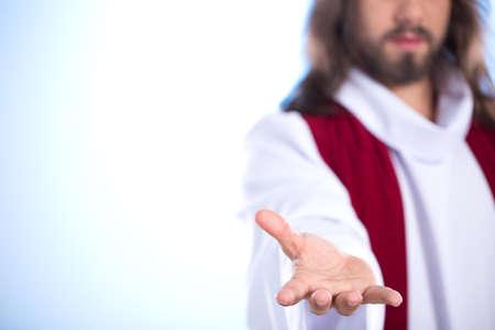 밝은 배경에 고립 된 손을 밖으로 도달하는 예수의 실루엣