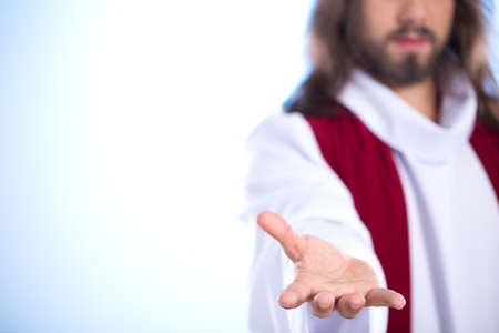 Silhouette of Jesus reaching out hand, isolated on bright background Stock Photo