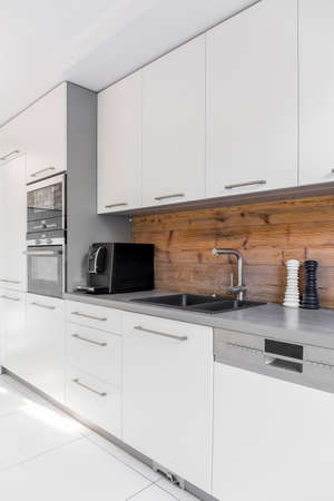 Functional kitchen with long countertop and white cabinets Stock Photo