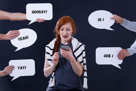 若い女性彼女のスマート フォンを使って友達と通信