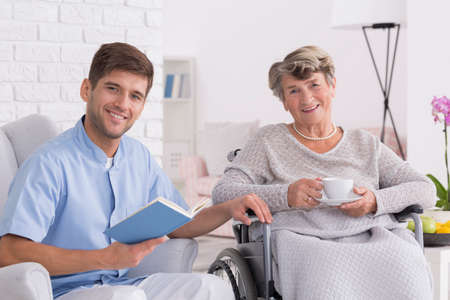 Smiling elegant senior woman on wheelchair with young male assistant