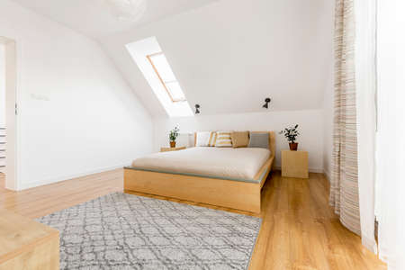 Attic bedroom with window, wood bed and floor panels Stock Photo