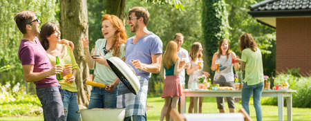 Pleasant meeting of smiled friends at a barbecue Stock Photo - 76347708