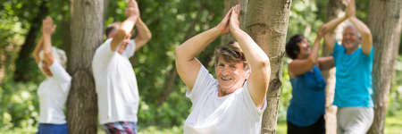 concentrate on: Yoga instructor helping elderly trainees with exercises during outdoor training