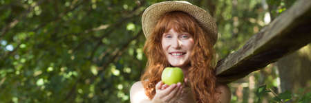 Smiling, red-haired girl with green apple both hands