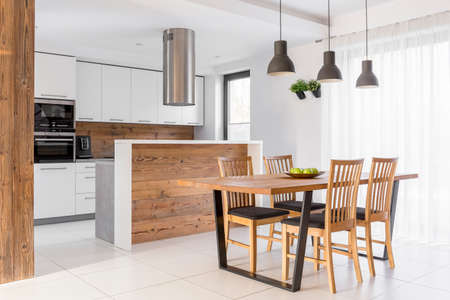 White kitchen with island, table and chairs Stock Photo