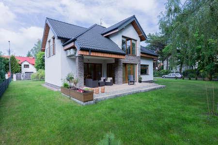 테라스가있는 분리 된 현대식 주택 외관은 녹색 잔디밭으로 둘러싸여 있습니다.