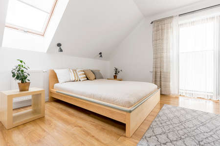Bright attic bedroom with wood double bed and floor panels