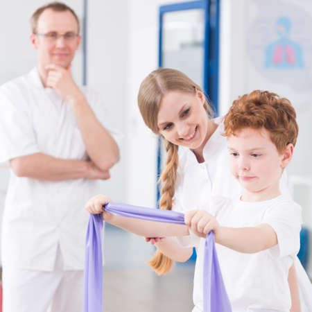 Boy strengthening the arm muscles during rehabilitation with professional physiotherapists