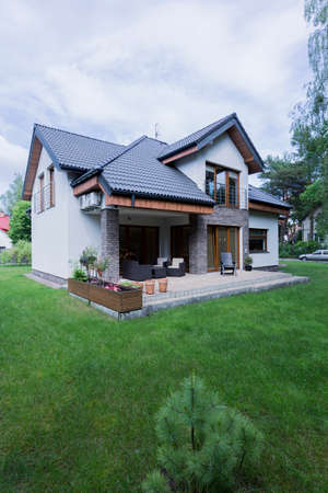 Big, elegant house with tiled roof and open patio area, surrounded by garden