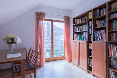 Romantic attic reading room with a large fitted book cabinet