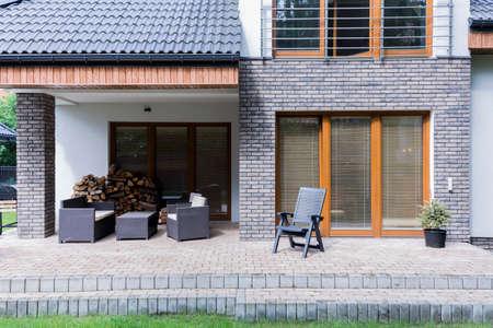 Geplaveide terras achter het moderne huis, met een set van donkere tuinmeubilair