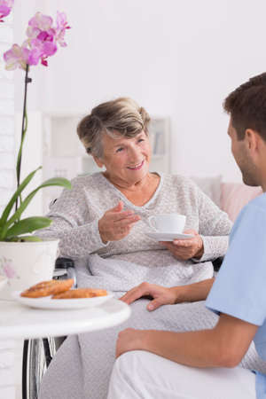 Grandmother talking with caregiver during tea time