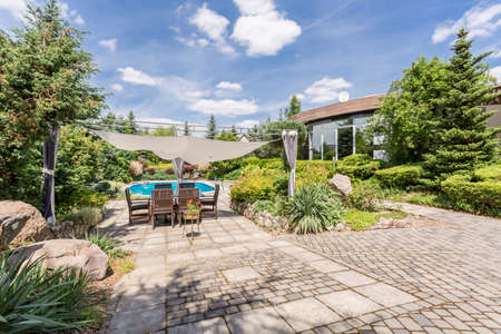 View of spacious garden with stone paths, garden furniture and swimming pool Фото со стока