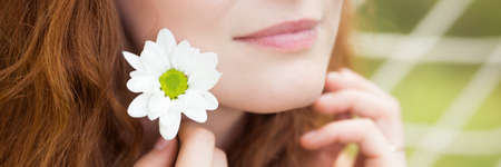 Natural beautiful woman with a fresh flower near her face