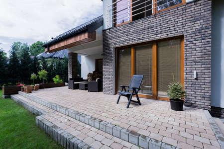 Klein beton terras met meubels in modern huis met baksteenhoogte