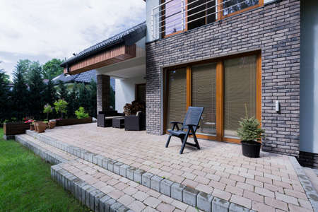 Small concrete terrace with furnitures in modern house with brick elevation Stockfoto