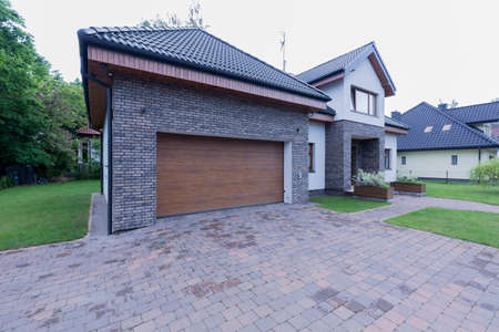 Large garage with automatic door and cobbled driveway by a detached house in the suburbs