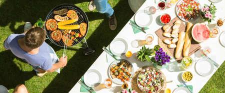 Feest in de open lucht met tafel vol eten en grill