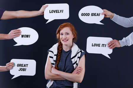 Hands holding speech bubbles with comments around a smiling woman Reklamní fotografie