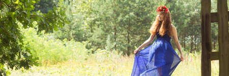 Woman in blue dress standing on the bosom of nature in the forest