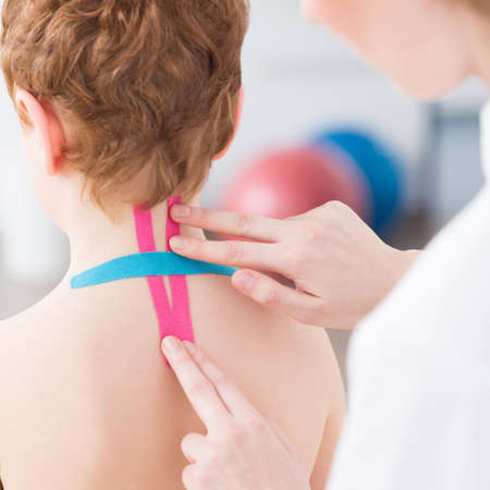 analgesics: Physiotherapist applying colorful kinesiology tapes during rehabilitation Stock Photo